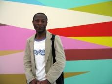 Olu Oguibe in front of a piece by Odili Donald Odita. Photo: Christine Eyene