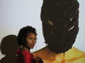 Ingrid Mwangi in front of Mwangi Hutter's video Masked (2000). Photo: Christine Eyene